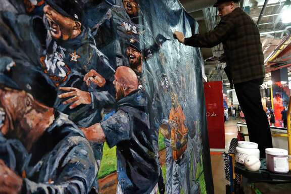 Opie Otterstad works on his giant painting  as Houston Astros fans walk by before the start of an MLB game at Minute Maid Park, Tuesday, July 10, 2018, in Houston.
