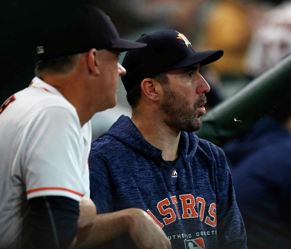 Houston Astros Justin Verlander spits seeds as he talks with manager AJ Hinch in the dugout during the fourth inning of an MLB game at Minute Maid Park, Thursday, July 12, 2018, in Houston.