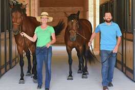 Owners Stacey Isles, with Nessie, and Mike Isles, with Charlotte, walk down the aisle in the stall area of their new barn at Graphite Hill Farm on Monday, July  9, 2018 in Greenfield, N.Y. The new farm was built for boarding horses. (Lori Van Buren/Times Union)