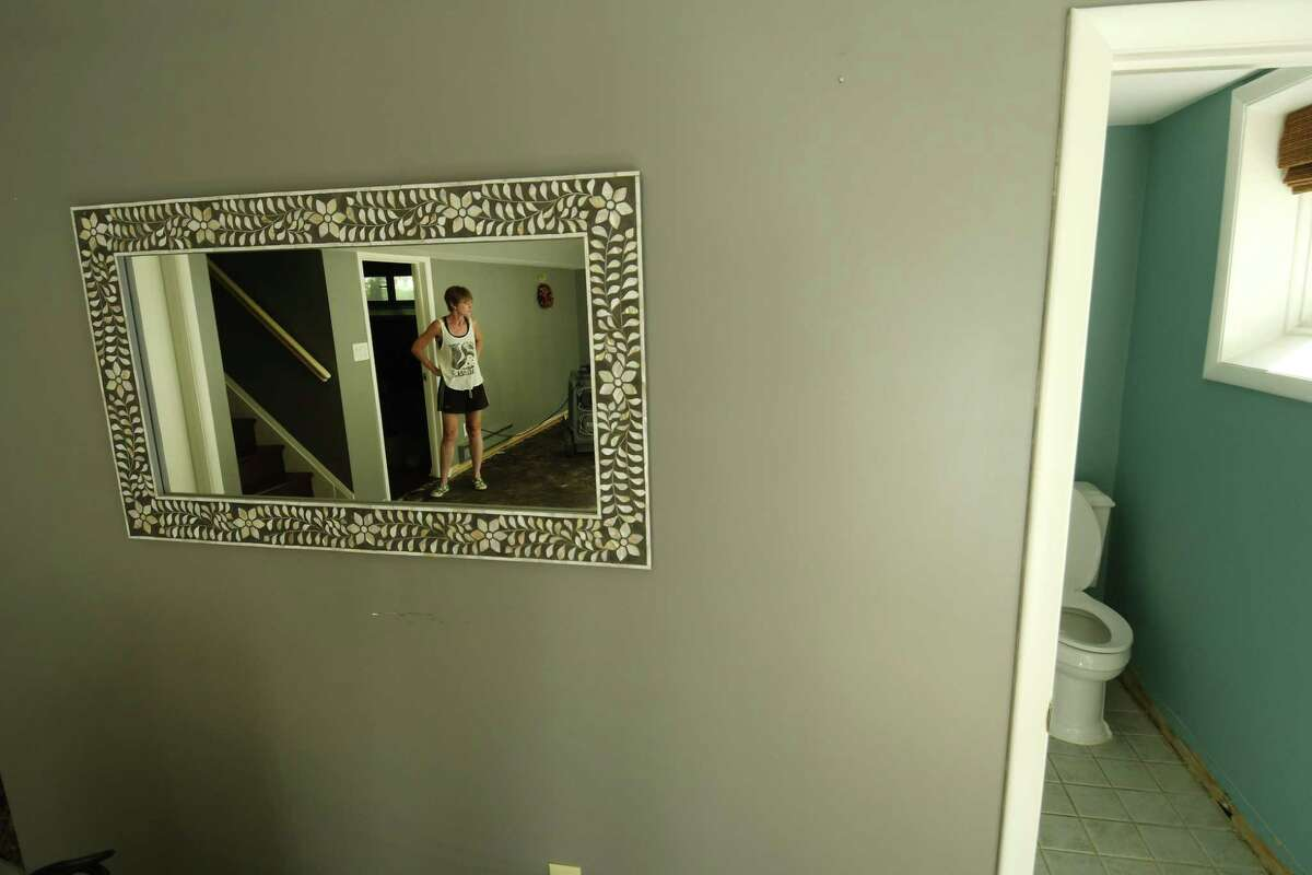 Stephanie Brown is reflected in a mirror in the damaged basement of her home on Marion Avenue, where on July 5th sewage poured out of a toilet in the basement, seen on the right, and flooded the space. Photo taken on Thursday, July 12, 2018, in Albany, N.Y. (Paul Buckowski/Times Union)
