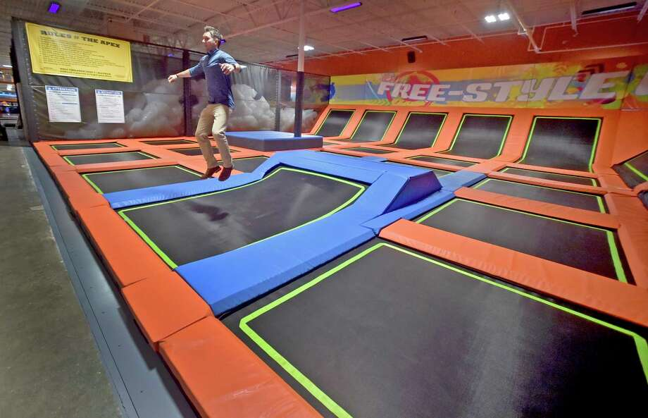 "Orange, Connecticut - Thursday, July 12, 2018: Urban Air Trampoline and Adventure Park corporate vice-president of marketing Josh Tate, demonstrates one of many trampolines in approximately 85,000 square feet of what Urban Air calls ""the ultimate adventure park"" on Bull Hill Lane in Orange. Urban Air, based in Texas, includes go carts that can reach 30 mph on a strait away, arcades, bowling, themed trampoline areas, a ninja warrior-style adventure course, a tube obstacle course, multiple climbing walls, a virtual reality game system, laser tag, modernized bumper cars, dodge ball, a unique ""Sky Rider"" coaster, a cafe among  other amusements. The opening of Urban Air is scheduled for Saturday, July 14th. Photo: Peter Hvizdak, Hearst Connecticut Media / New Haven Register"