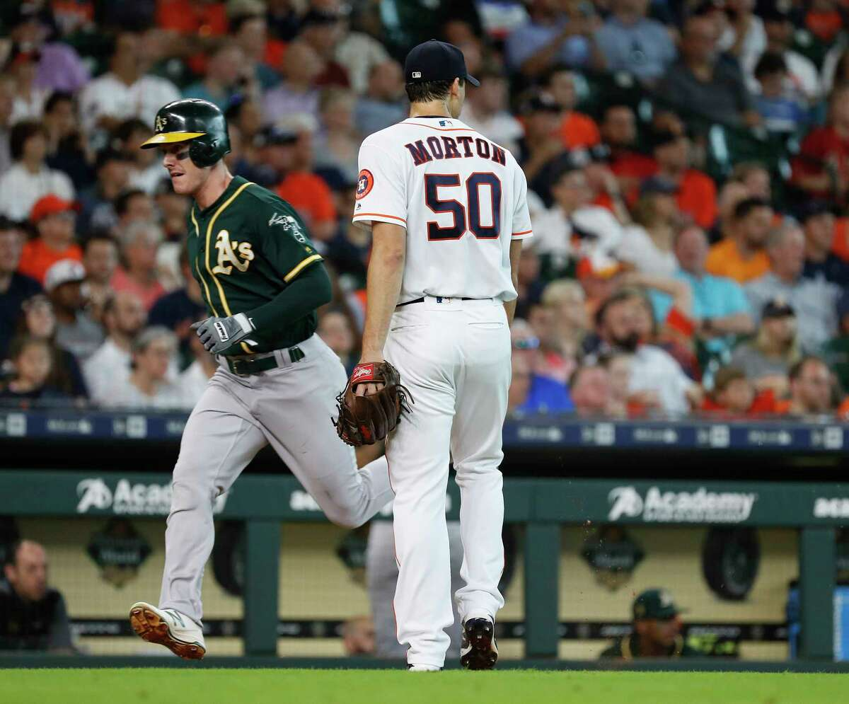 Oakland Athletics Mark Canha (20) trots home, past Houston Astros starting pitcher Charlie Morton (50) after Nick Martini hit an RBI double during the fifth inning of an MLB game at Minute Maid Park, Thursday, July 12, 2018, in Houston.