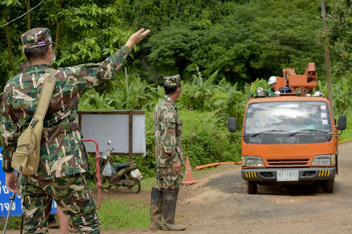 Thai soldiers (L) stand on the roadside as a truck leaves the Tham Luang cave area in Khun Nam Nang Non Forest Park in the Mae Sai district of Chiang Rai province on July 12, 2018, two days after the last boys and coach were rescued after being trapped in the cave. Rescuers dismantled on July 12 the site of the successful operation to extract 12 footballers and their football coach trapped for two weeks in a cave, a mission of unprecedented scale for Thailand that is already garnering movie interest. / AFP PHOTO / TANG CHHIN SothyTANG CHHIN SOTHY/AFP/Getty Images