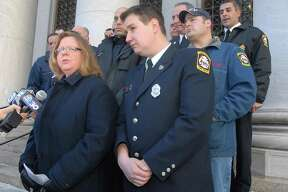 In this Jan. 2009 file photo, attorney Karen Torre speaks to the press on the steps of the Federal Courthouse. Frank Ricci, center, was the lead plaintiff in the the New Haven 20's reverse-discrimination case, which the U.S. Supreme Court had announced Friday it would hear.