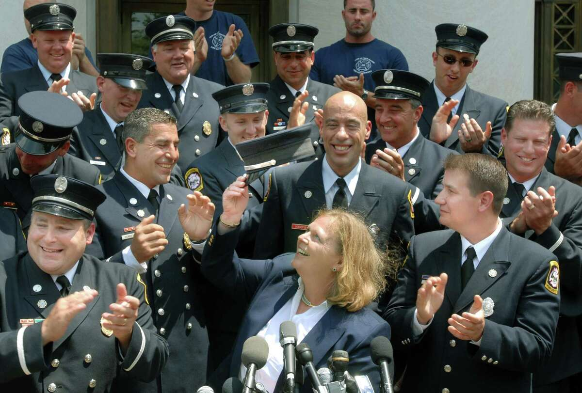 In this June 29, 2009 file photo, on the steps of the Federal Court House, New Haven: attorney Karen Torre raises a firefighter's hat, with plaintiffs in the Ricci vs. DeStefano Supreme Court case. Frank Ricci, lead plaintiff is front right.