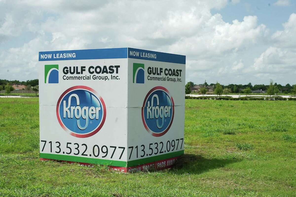 Landscaped paved roads and a parking lot lie behind a sign marking the site of a proposed Kroger store in Pearland.