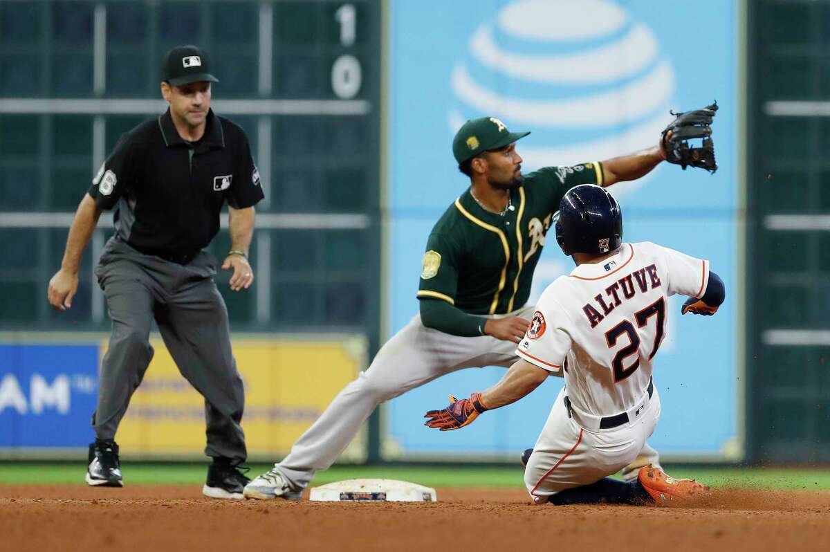 Houston Astros Jose Altuve (27) is tagged out at second base by Oakland Athletics Marcus Semien after Altuve tried to stretch a single into a double during the seventh inning of an MLB game at Minute Maid Park, Thursday, July 12, 2018, in Houston.