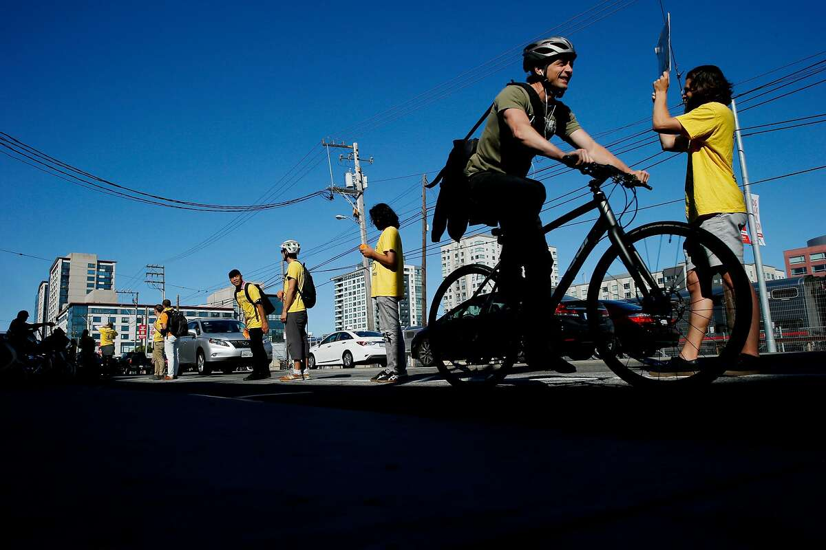 Activists of the People Protected Bike Lane group form a human barrier to separate the car lane from the bike lane, Tuesday, July 10, 2018, in San Francisco, Calif. The demonstration was along Townsend Street between 4th and 5th streets.