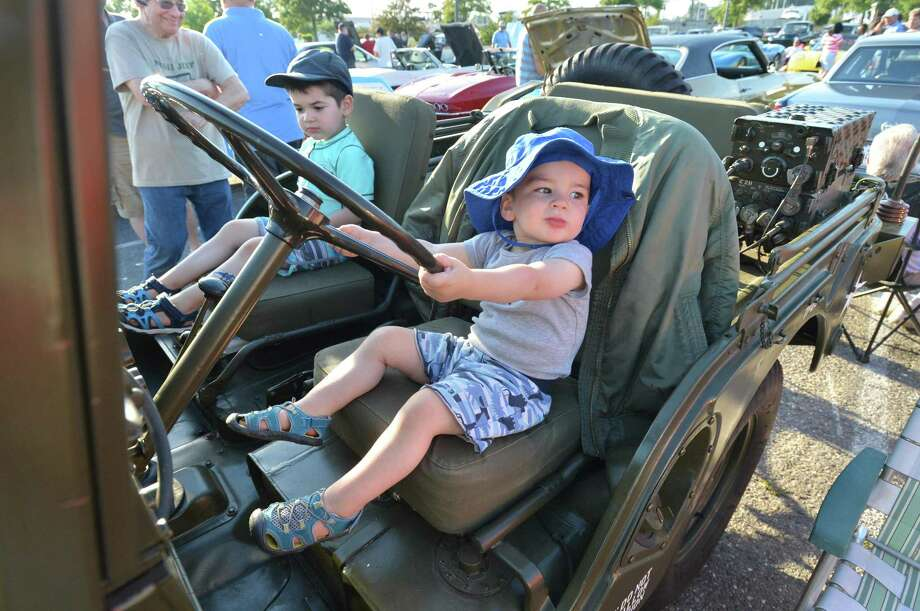 Two-year-old Ben Novak and his brother, 4-year-old Cameron, can't reach the gas pedals but enjoy a moment sitting in Gene Sutterberg's 1955 M38A1 Willys military jeep during the Coachmen Rod and Custom car club's Beach Cruise on Tuesday July 10, 2018 at Calf Pasture Beach in Norwalk. More than 100 cars were present and judged for trophies. The next show is Aug. 14 at Calf Pasture. Photo: Alex Von Kleydorff / Hearst Connecticut Media / Norwalk Hour