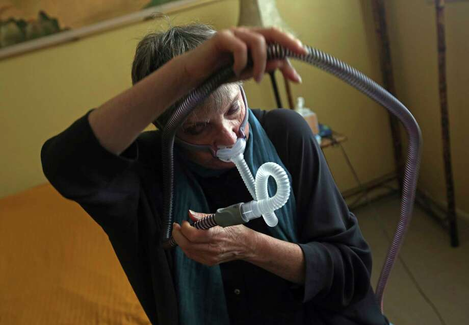"""Joelle Dobrow demonstrates how she puts on her sleep apnea breathing device at her home in Los Angeles Thursday, July 12, 2018. It's been two decades since doctors fully recognized that breathing that stops and starts during sleep is tied to a host of health issues, even early death, but there still isn't a treatment that most people find easy to use. Dobrow said it took her seven years to find one she liked. """"I went through 26 different mask styles,"""" she said. """"I kept a spreadsheet so I wouldn't duplicate it."""" Photo: Reed Saxon, AP / Copyright 2018 The Associated Press. All rights reserved. This material may not be published, broadcast, rewritten or redistribu"""