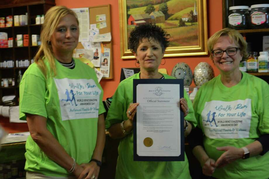 Organizer Pam Pinto, center, owner of Act Natural Health and Wellness store, shows proclamation from Gov. Dannel Malloy naming July 11 as World Benzodiazepine Awareness Day in Connecticut Photo: Leslie Hutchison / Hearst Connecticut Media /
