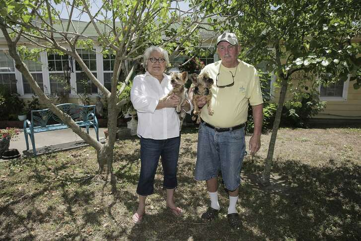 Lynda and David Bates hold two of their four dogs, Joy and Sally, in front of their Galveston home on Tuesday, June 12, 2018 in Galveston. The couple rebuilt their home after Hurricane Ike, but was never told it should be elevated or demolished.