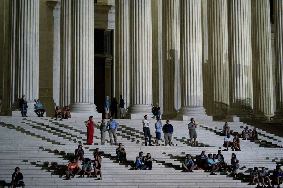 People sit and stand on the steps of the Supreme Court after President Donald Trump announced his nominee to the Supreme Court July 9. If confirmed Judge Brett Kavanaugh, President Trumps new nominee, would be the sixth Catholic justice. Photo: ERIN SCHAFF /NYT / NYTNS