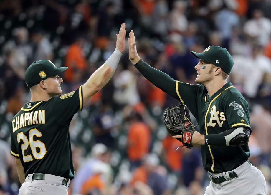 Matt Chapman and Mark Canha celebrate after Oakland's come-from-behind, 6-4 victory over the Astros on Thursday. Photo: David J. Phillip / Associated PressP / Copyright 2018 The Associated Press. All rights reserved