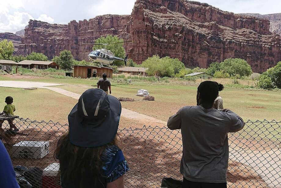A helicopter lands Thursday at the Havasupai reservation in Arizona to evacuate tourists caught in flash flooding at a popular campground on tribal land near the Grand Canyon. Photo: Benji Xie
