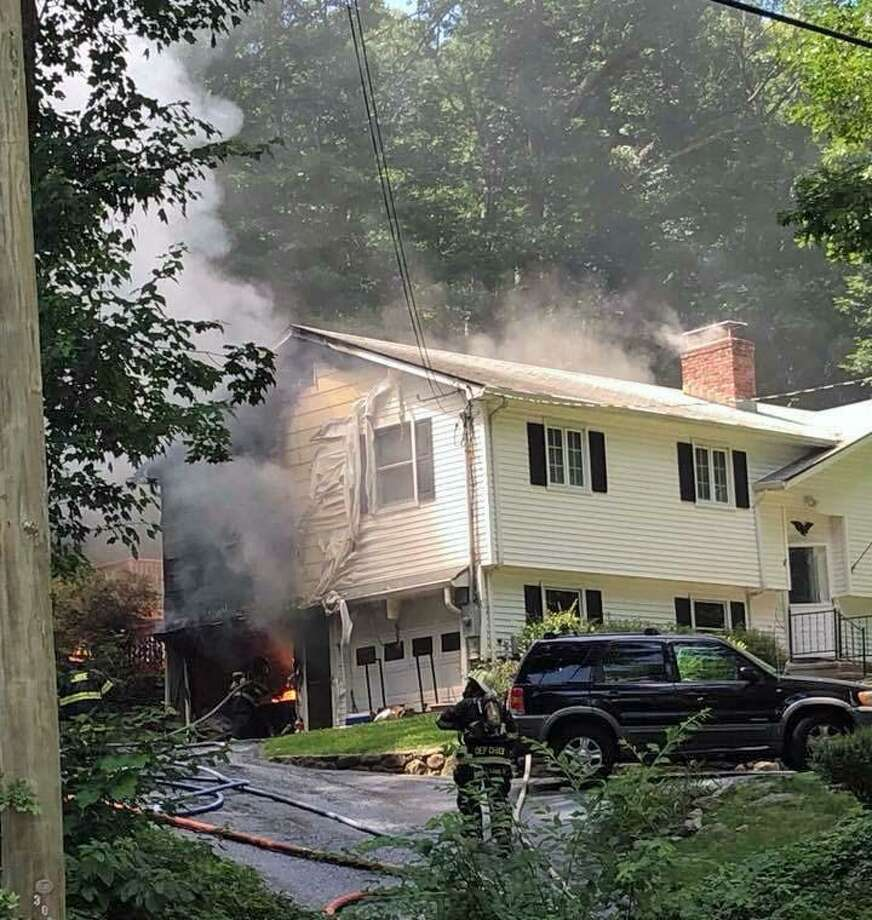 A house fire broke out on Greenwood Lane in Monroe, Conn., on July 12, 2018, around 2:30 p.m. Several fire units responded to the scene and reported seeing heavy fire from the attached garage caused by a car that had caught fire. Photo: Contributed Photo / Monroe Volunteer Fire Department / Contributed Photo / Connecticut Post Contributed