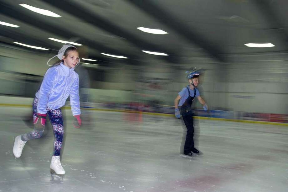 10-year-old Elaina Nowik of Norwalk, left, and nine-year-old Kane Duggar of New Canaan, zip around the ice together during the youth summer camp at Stamford Twin Rinks on Hope St. in Stamford, Conn. on Thursday, July 12, 2018. Photo: Michael Cummo / Hearst Connecticut Media / Stamford Advocate