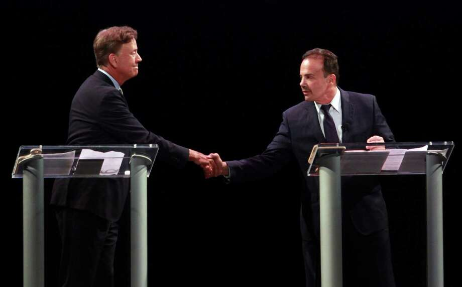 Ned Lamont, left, shakes hands with Bridgeport Mayor Joe Ganim before the start of the first Democratic debate for governor at the Shubert Theater in New Have on Thursday. Photo: Christian Abraham / Hearst Connecticut Media / Connecticut Post