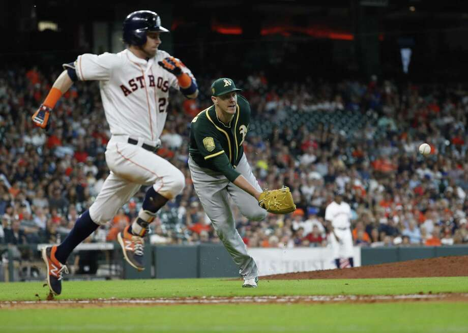 After getting to a bunt by Josh Reddick, A's pitcher Ryan Buchter shovels the ball to first base with his glove for the second out in the Astros' eighth. Photo: Karen Warren, Staff / Houston Chronicle / © 2018 Houston Chronicle