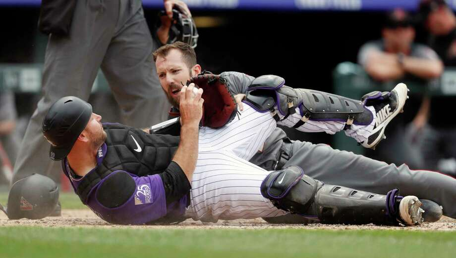 Colorado Rockies catcher Chris Iannetta, front, holds up the ball to show Arizona Diamondbacks' Steven Souza Jr. that he was tagged out at home plate while trying to advance from third base on a ground ball hit by catcher John Ryan Murphy in the sixth inning of a baseball game Thursday, July 12, 2018, in Denver. (AP Photo/David Zalubowski) Photo: David Zalubowski / Copyright2018 The Associated Press. All rights reserved.
