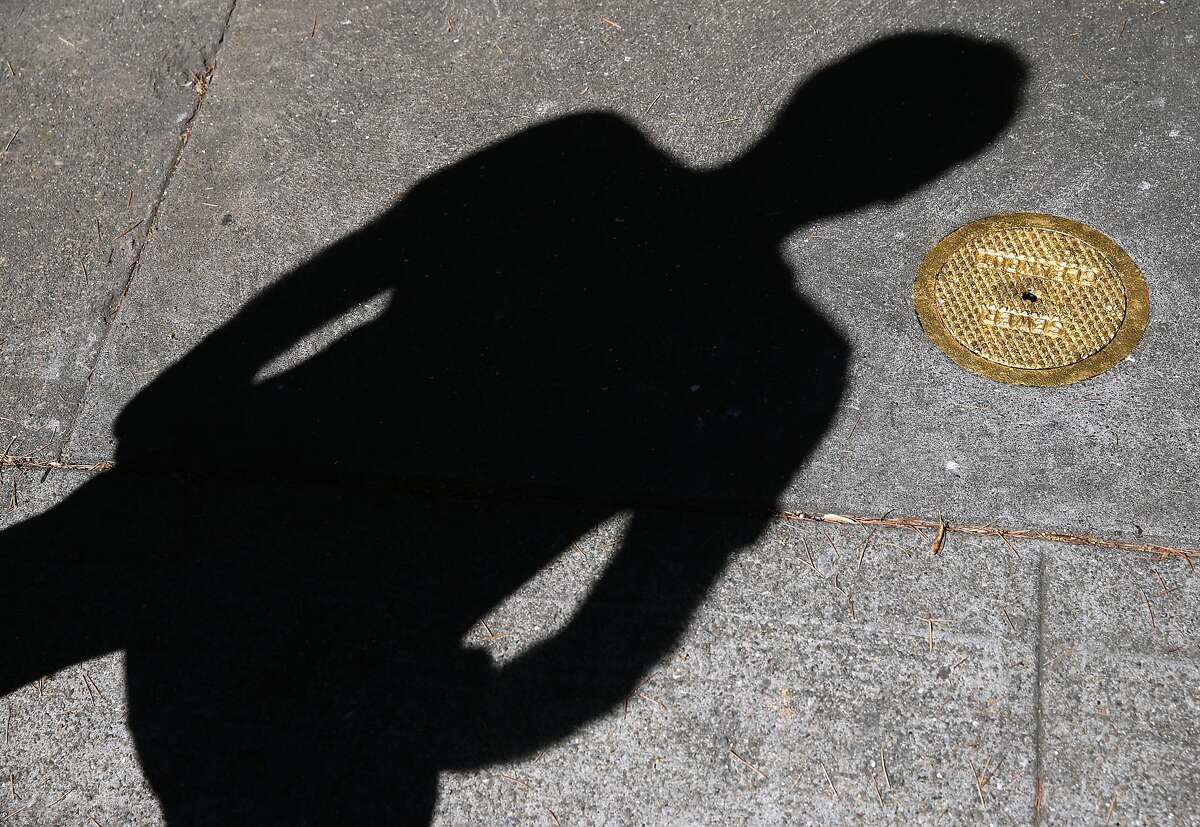 """Erik Schmitt casts a shadow over a sewer cleanout cover gilded in gold on Acton Circle in Berkeley, Calif. on Saturday, July 7, 2018. For his Gilded Cities art project, artist Erik Schmitt covered a number of utilitarian objects around the Bay Area with 23 karat gold leaf to convey the idea that the region has become """"an enclave for the rich."""""""
