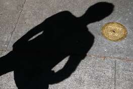 "Erik Schmitt casts a shadow over a sewer cleanout cover gilded in gold on Acton Circle in Berkeley, Calif. on Saturday, July 7, 2018. For his Gilded Cities art project, artist Erik Schmitt covered a number of utilitarian objects around the Bay Area with 23 karat gold leaf to convey the idea that the region has become ""an enclave for the rich."""