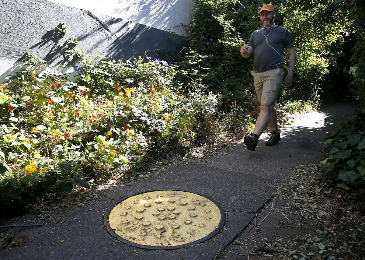 """Adam Young walks toward a manhole cover gilded with gold leaf on Indian Rock Path in Berkeley, Calif. on Saturday, July 7, 2018. For his Gilded Cities art project, artist Erik Schmitt covered a number of utilitarian objects around the Bay Area with 23 karat gold leaf to convey the idea that the region has become """"an enclave for the rich."""""""