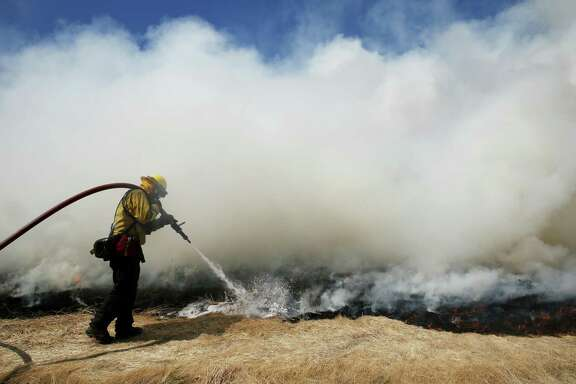 Marin County Fire Department firefighter trainee Alex Mercer puts out the fire during wildfire training in San Rafael on Wednesday, June 13, 2018.
