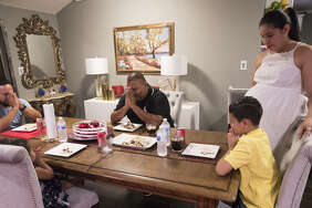 Luis Figueroa, center, 30, encourages his children to pray before eating, Monday, May 21, 2018, in Houston. Luis, who is original of Honduras and was brought to Houston as a child, is concerned about their future as they are losing their TPS (Temporary Protected Status) designation that have kept him legally in the United States for more than a decade.