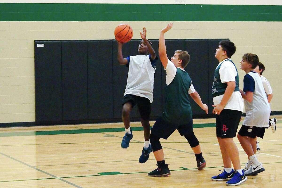Jordan Woodson shoots a layup past Aelias Saad Thursday during the Clear Falls summer basketball camp.