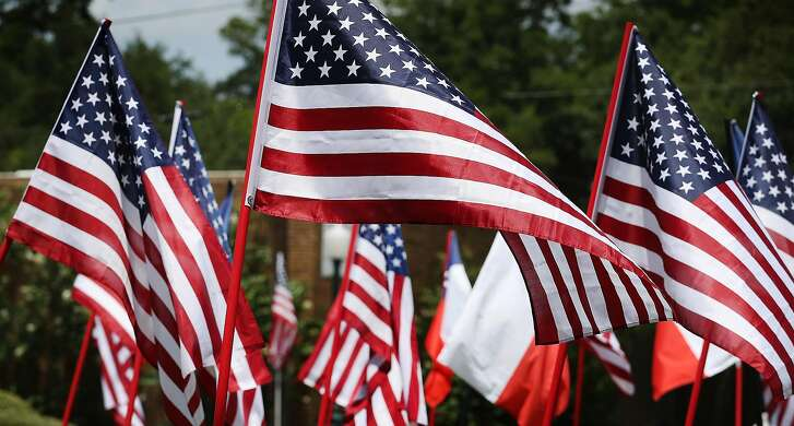 Flags wave in the wind Monday, July 2, 2018, in League City. Larry Westfall and his wife, Lesli, ?have ?sold U.S. flags on the corner of FM 518 and Butler in downtown League City since 1991.? ( Steve Gonzales / Houston Chronicle )