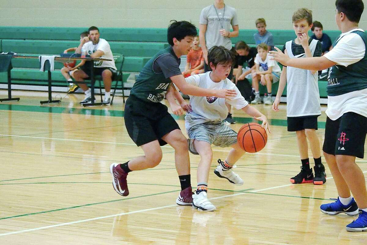 Anakin Reddington defends as Carson Timmons dribbles the ball in the lane Thursday during a scrimmage at the Clear Falls summer basketball camp.