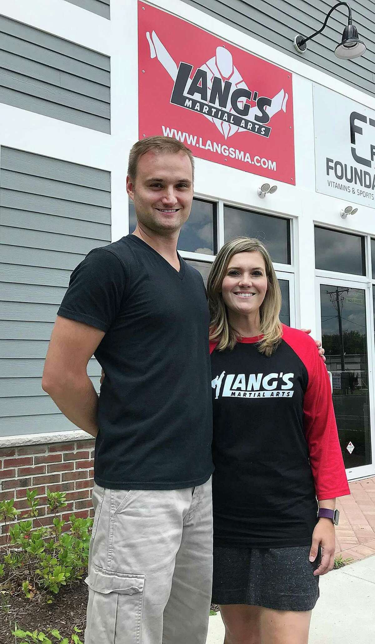 Joe and Teresa Lang of Lang's Martial Arts stand outside of their new studio in Brookfield, Conn., on Wednesday, July 11, 2018.