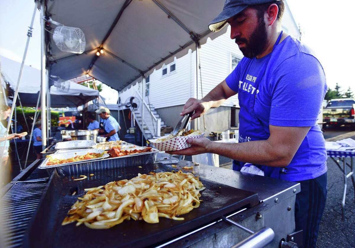 Phil Lodato of Greenwich prepares a chicken, peppers and onion feast at the St. Catherine of Siena Church annual Carnival of Fun. The community event, which features food, games and carnival rides, runs through Saturday.