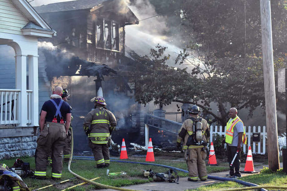 Hoses douse the charred remains of a house at 322 M. St. Thursday evening. The front porch of the house was fully involved when Edwardsville Fire Department personnel arrived at the scene, and it had moved to the second floor and into the attic. No one was inside the house at the time of the fire, which was still under investigation Friday. Photo:     Matthew Kamp/Intelligencer