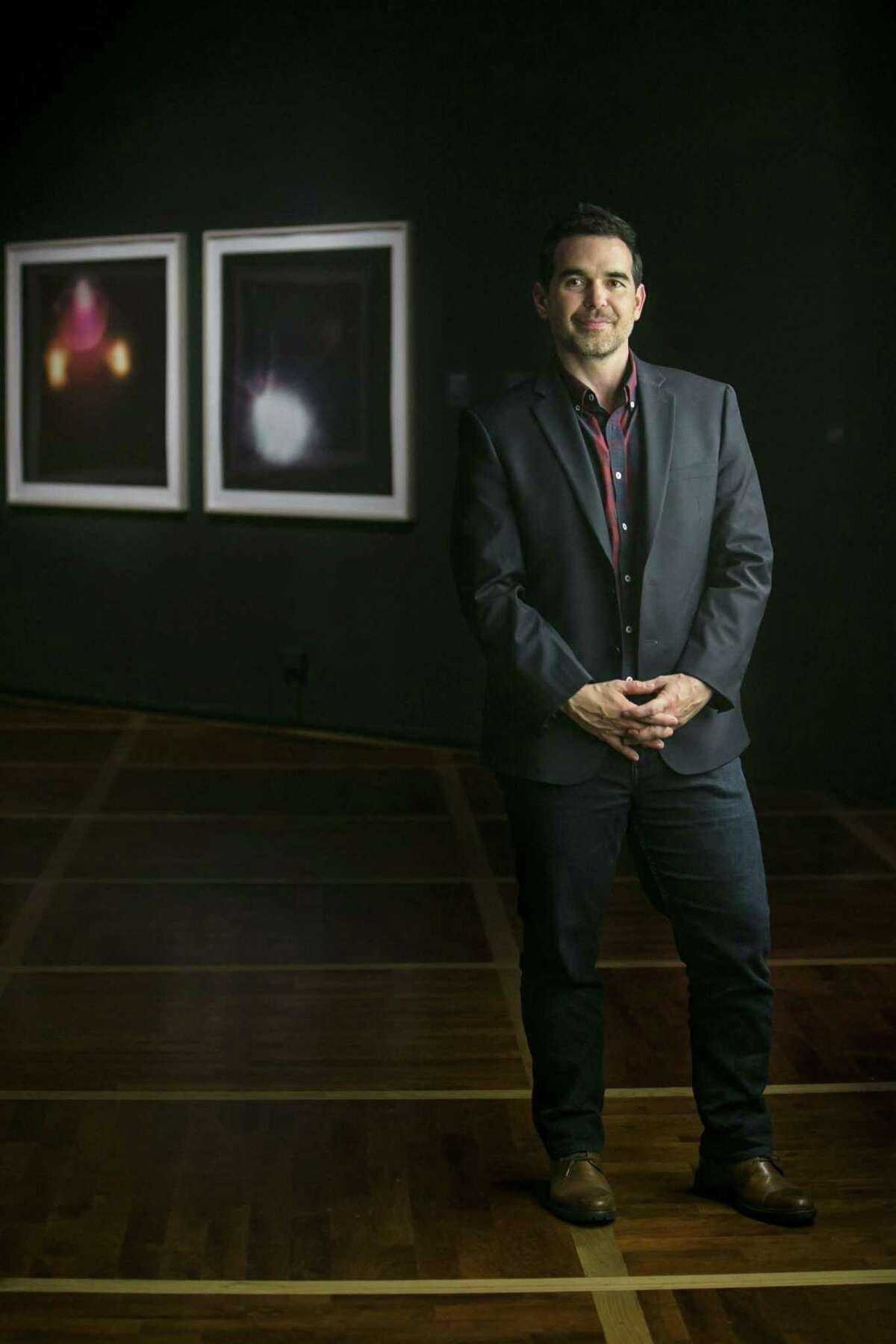 """Dario Robleto poses beside prints created from album covers that include images of stage lights from the shows of now-deceased musicians, a series called """"The Sky, Once Choked with Stars, Will Slowly Darken."""" The prints are among works on view in Robleto's solo show """"Ancient Beacons Long for Notice"""" at the McNay."""