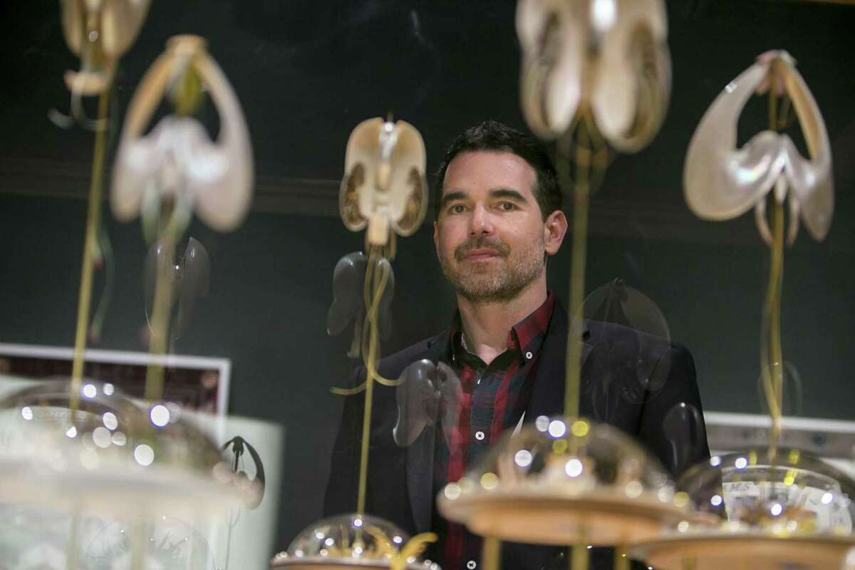 Dario Robleto poses with a new glass-enclosed sculptural assemblage created for his show at the McNay.