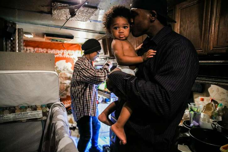 Arnell Clark embraces his son Arnez Clark, 1, while his girlfriend Mataele Robertson (left) gets his formula ready in their RV in East Palo Alto, California, on Thursday, July 12, 2018. They moved to an RV after their rent went up in 2015.