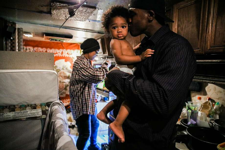 Arnell Clark embraces son Arnez Clark, 1, while girlfriend Mataele Robertson gets the boy's formula ready in their RV in East Palo Alto. They moved to an RV after their rent went up. Photo: Gabrielle Lurie / The Chronicle