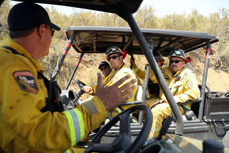 Cal Fire Deputy Chief Mike van Loben Sels (left) strategizes with Monty Smith and Felix Berbena during County Fire in Yolo County, Calif. on Thursday, July 5, 2018. Photo: Scott Strazzante / The Chronicle