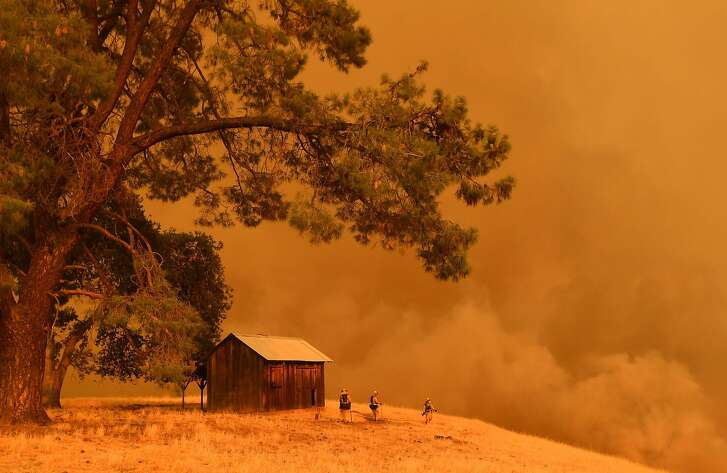 In this file photo taken on July 1, 2018 firefighters watch as flames from the County Fire climb a hillside in Guinda, California.  The western US was in the midst of a record heat on June 6, 2018, sparking in some areas  dozens of massive fires that required the evacuation of hundreds of people, with a civilian casualty reported in California and the declared state of emergency near San Diego. / AFP PHOTO / JOSH EDELSONJOSH EDELSON/AFP/Getty Images