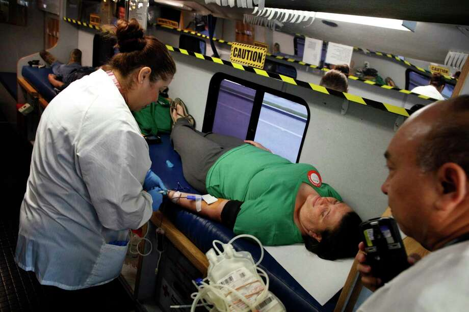 Phlebotomist Nancy Del Campo collects blood from Jessi Baden, who is donating for all of her friends unable to because of laws that prohibit gay or bisexual men from donating themselves. (Barbara Davidson/Los Angeles Times/TNS) Photo: Barbara Davidson / Los Angeles Times