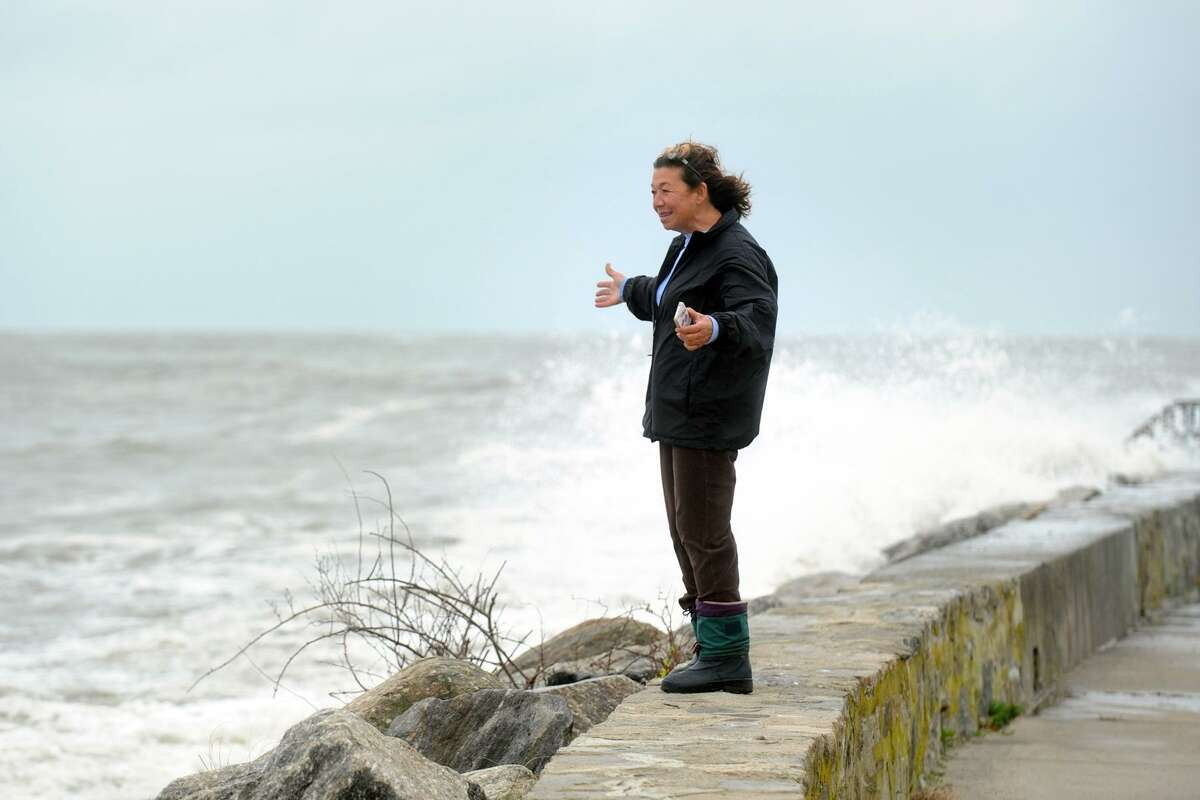 FILE PHOTO - Tomiko Knapp watches storm waters from sea wall along Beach Drive, in the Lordship section of Stratford, Conn. Oct. 29th, 2012.