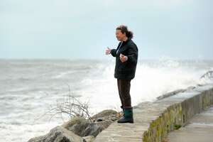 FILE PHOTO — Tomiko Knapp watches storm waters from sea wall along Beach Drive, in the Lordship section of Stratford, Conn. Oct. 29th, 2012.