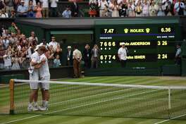 South Africa's Kevin Anderson (R) embraces US player John Isner after winning their men's singles semi-final match on the eleventh day of the 2018 Wimbledon Championships at The All England Lawn Tennis Club in Wimbledon, southwest London, on July 13, 2018. Anderson won the match 7-6, 6-7, 6-7, 6-4, 26-24. / AFP PHOTO / Oli SCARFF / RESTRICTED TO EDITORIAL USEOLI SCARFF/AFP/Getty Images