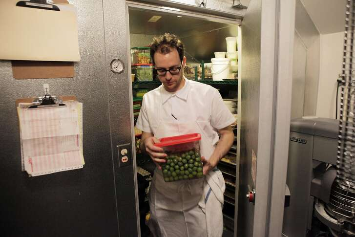 Head Chef Josh Even brings olives out of the walk-in refrigerator at Tosca on Monday. The walk-in was put in the space previously taken by the office and phone booth at the bar. San Francisco's legendary Tosca is set to reopen this week under new ownership, featuring a restaurant as well as the bar. April Bloomfield of Spotted Pig helms the dining, and Co-owner Ken Friedman hopes the changes will bring back regulars and a new crowd. The San Francisco, Calif., mainstay is seen here on Monday, October 7, 2013.