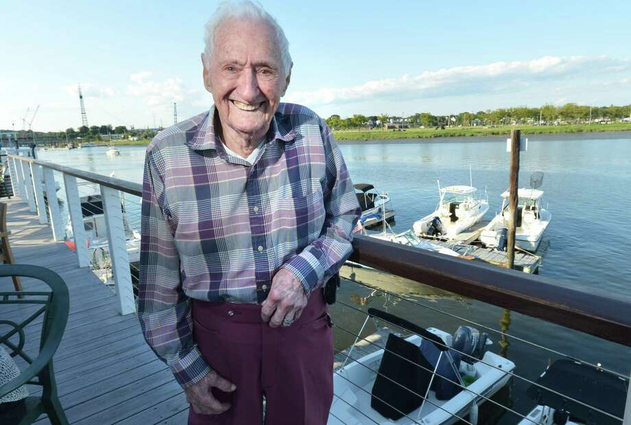Harold Scudder stands on the deck at Ischoda Yacht Club on Thursday July 12, 2018 where he will celebrate is 95th birthday as the oldest living member of the club in Norwalk Conn. Photo: Alex Von Kleydorff / Hearst Connecticut Media / Norwalk Hour