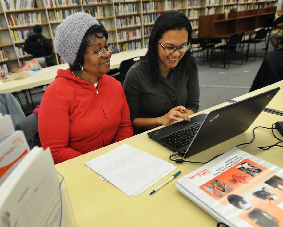 Dionne Williams, left, of Bridgeport, signs up for health insurance with Access Health CT enrollment specialist Rosalina De Los Santos at the Bridgeport Public Library at 925 Broad Street in downtown Bridgeport, Conn. on Tuesday, November 18, 2014. On July 10, 2018, the federal government announced it was cutting grant money for its navigator program, which helps fund people who assist in health care enrollment. The cuts aren't expected to directly affect Connecticut, but experts said there could be some repercussions. Photo: Brian A. Pounds / Brian A. Pounds / Connecticut Post