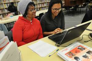 Dionne Williams, left, of Bridgeport, signs up for health insurance with Access Health CT enrollment specialist Rosalina De Los Santos at the Bridgeport Public Library at 925 Broad Street in downtown Bridgeport, Conn. on Tuesday, November 18, 2014. On July 10, 2018, the federal government announced it was cutting grant money for its navigator program, which helps fund people who assist in health care enrollment. The cuts aren't expected to directly affect Connecticut, but experts said there could be some repercussions.