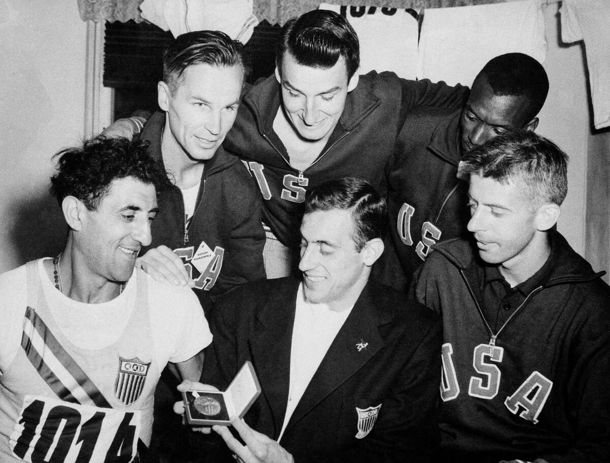 Lindy Remigino, center, displays the medal he received after winning the 100 meter final at the Summer Olympics in Helsinki in 1952.